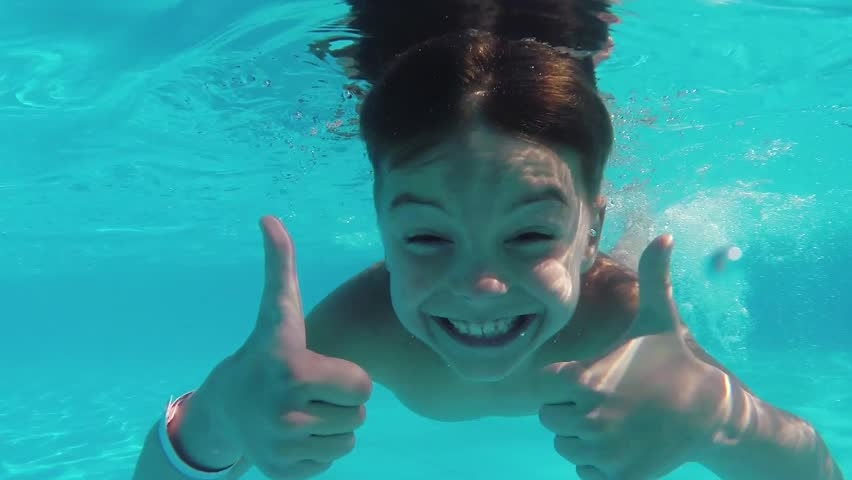 Cute teen boy dives in blue pool with open eyes #9735068