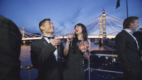 4K Attractive Asian couple chatting on boat deck during party at night