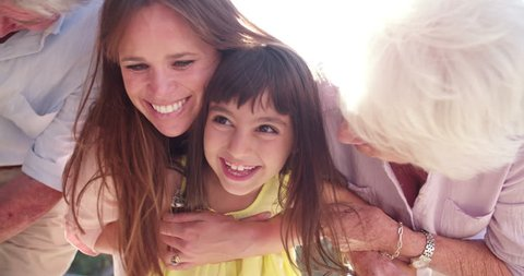 Laughing little girl having fun with her mother and grandmother outdoors in Slow Motion