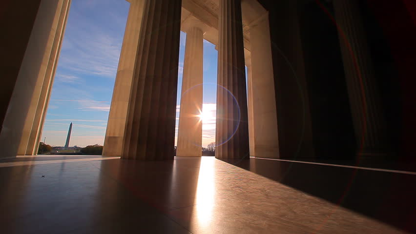 Lincoln Memorial in Washington, DC,United States Government -  tracking shot with sun lens flare  between the bottom of the pillars.