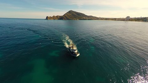 A commercial fishing boat entering harbor with seagulls flying around - aerial flying over wide angle view 4k Ultra HD