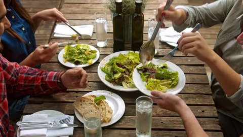 Above shot of healthy multicultural group of young people eating salad,  aerial view organic food togetherness concept.