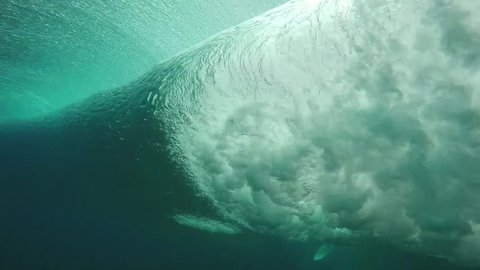 Underwater view of surfer trying to dive under wave breaking over coral reef, slow motion