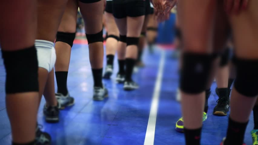 Shot of legs of Volleyball players congratulating each other after an Indoor game. Unrecognizable people on the shot wearing knee pads