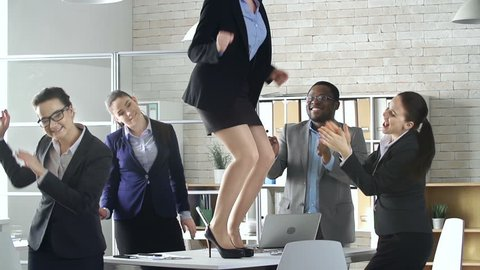 Multinational business team of five celebrating successful deal with a dance in the office