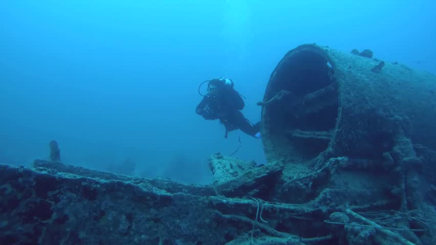 RED SEA, STRAIT OF GUBAL, EGYPT - OCTOBER, 2014:  diver inspects locomotive crashed on board the wreck SS Thistlegorm, Red Sea, Sharm el Sheikh, Egypt, Sinai   | Shutterstock HD Video #9895658