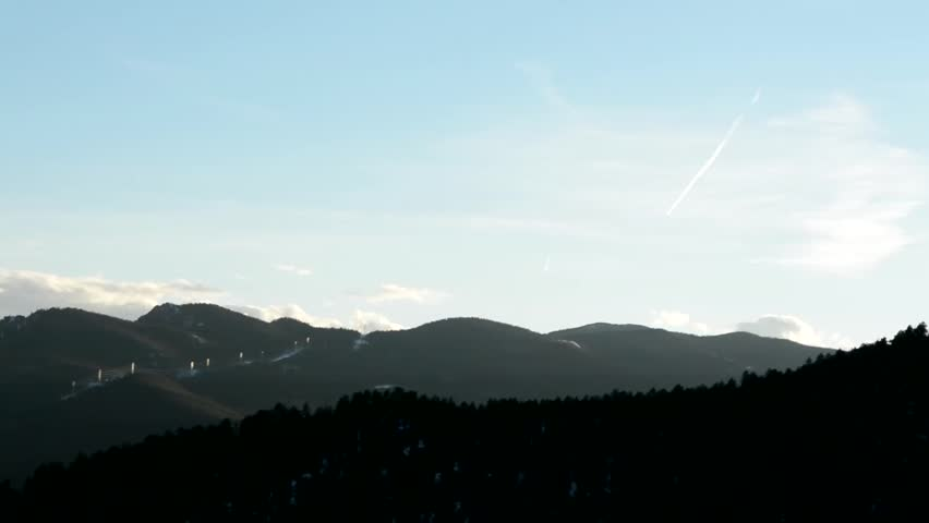 Contrails and power lines on mountain peak