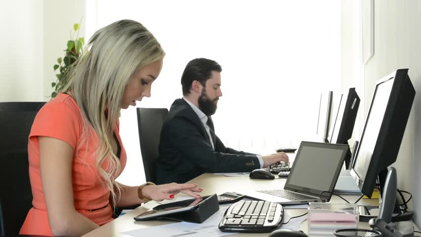 Woman works on tablet and man works on desktop computer in the office (workers) | Shutterstock HD Video #9930968