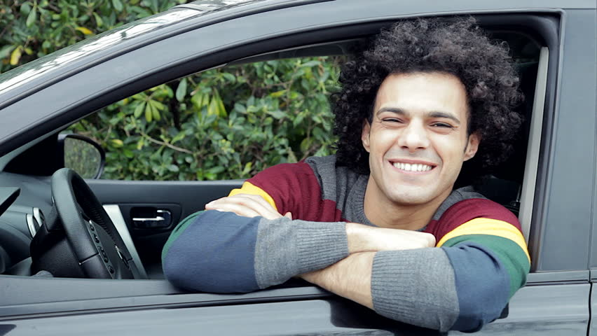 young cool man saying hello from car