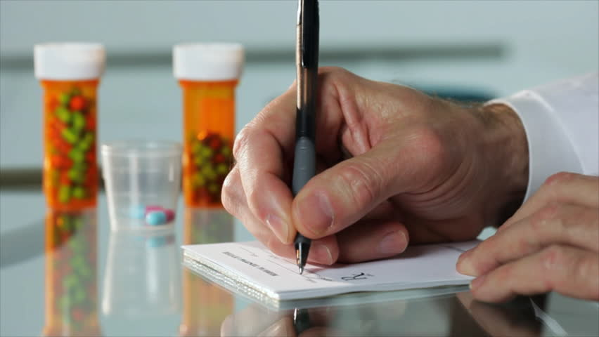 A close up of a male physician's hand writing out a prescription with out of focus pharmaceuticals pill bottles in the background.