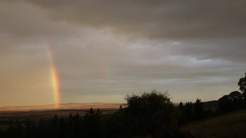 Camera pans left and then right over Dalgety plains at sunset with rainbow. Video shot overlooking Dalgety plains, NSW Australia