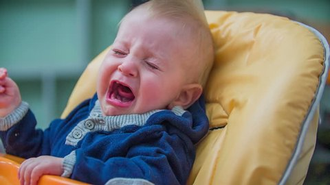Hungry baby boy in a chair. Young boy is seating in the eating chair in kitchen and is crying because he is hungry, footage in slow motion.